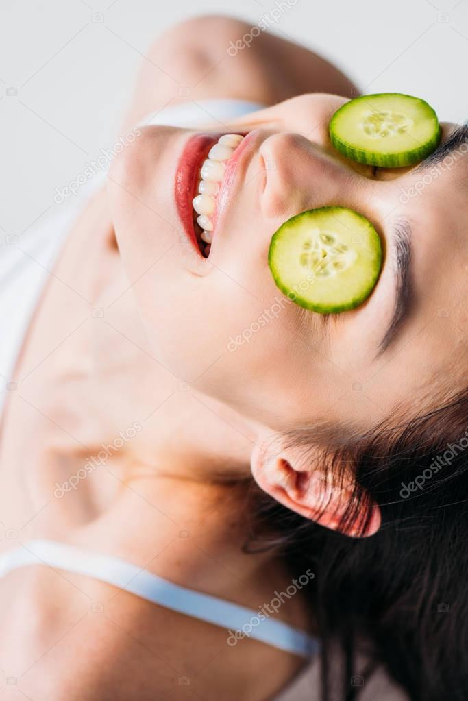 Smiling woman with cucumber eye mask