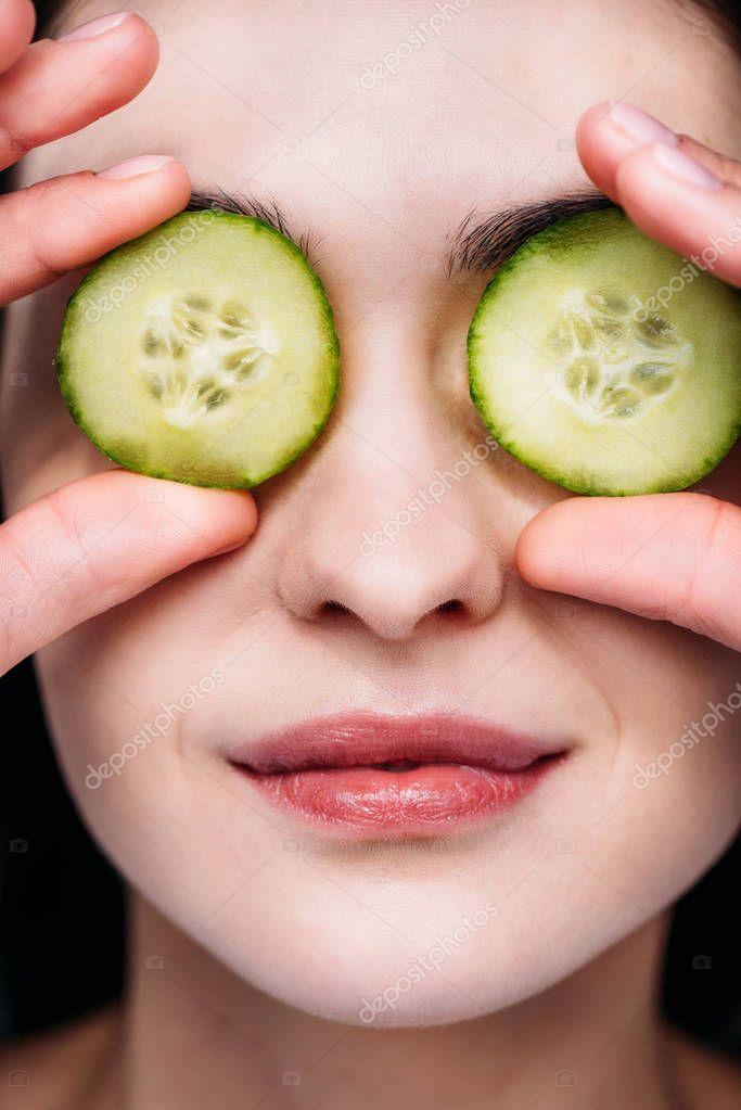 Woman applying cucumber eye mask