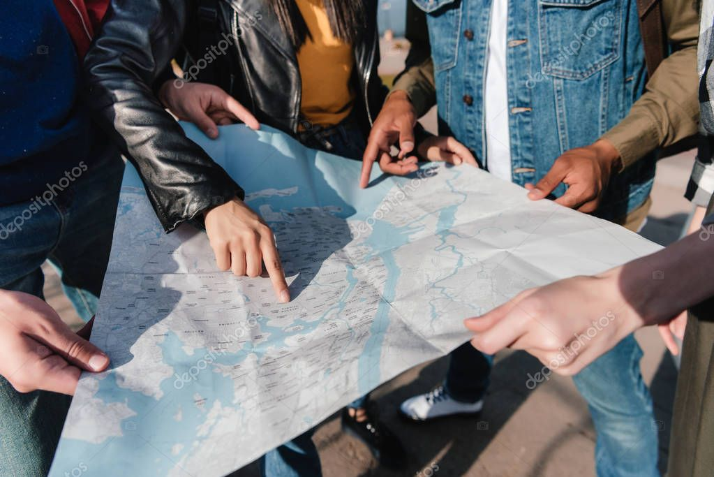 multiethnic friends pointing at map