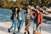 multicultural friends walking on pier