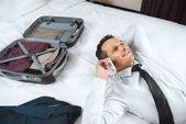 Geschäftsmann telefoniert auf dem Bett