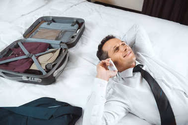 Businessman talking on phone on bed