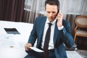 Fotografie businessman holding paperwork and talking on phone