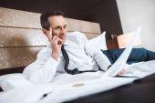 Fotografie Businessman on bed reading paperwork
