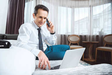 businessman on phone using laptop