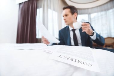 Young businessman in formal suit sitting in hotel room and reading some paperwork and holding cup of coffee stock vector