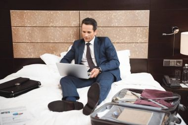 businessman on bed using laptop