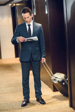 businessman with suitcase reading newspaper