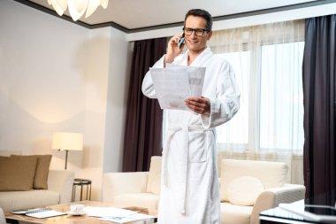Businessman in bathrobe talking on phone