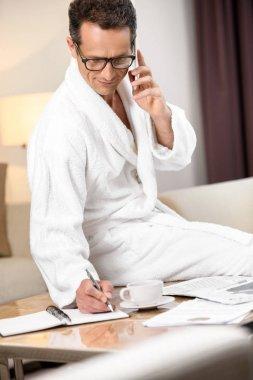 Businessman in bathrobe taking notes