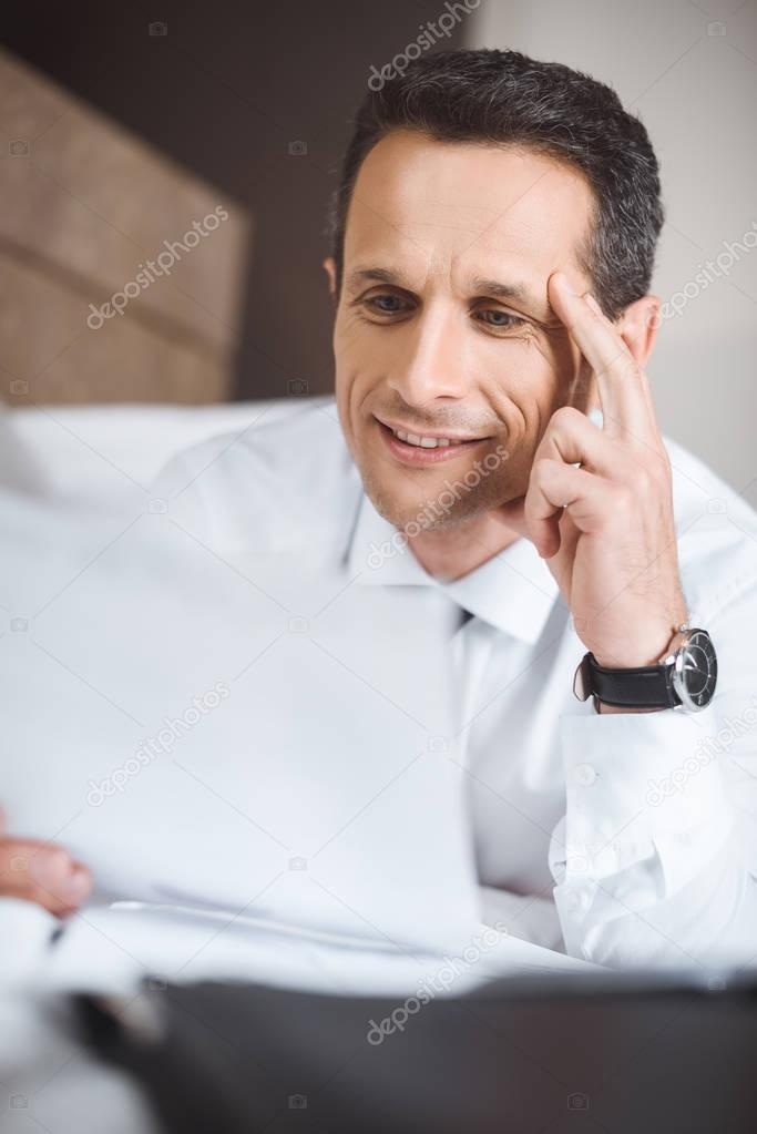 Businessman on bed reading paperwork