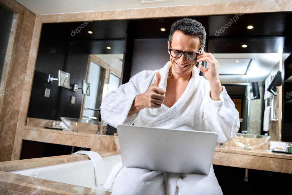 Businessman in bathrobe working with devices