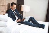 Fotografie podnikatel na posteli pomocí přenosného počítače