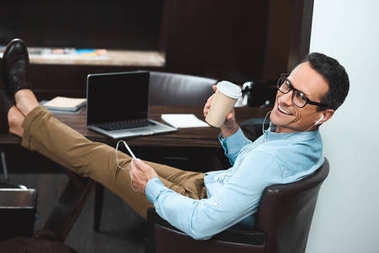 Businessman in headphones with coffee cup