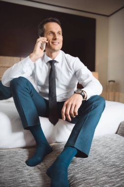 businessman on bed talking on phone
