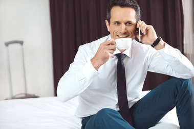 Businessman drinking coffee and talking on phone