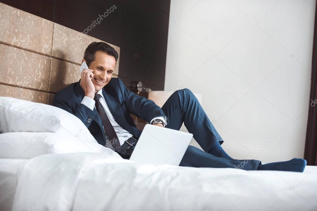 businessman on bed with laptop and phone