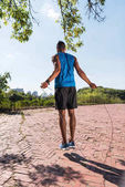 Photo sportsman jumping on skipping rope