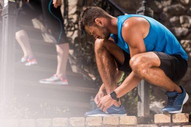 sportsman tying shoelaces