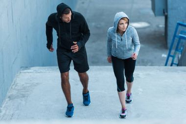 sportswoman and sportsman jogging on stairs