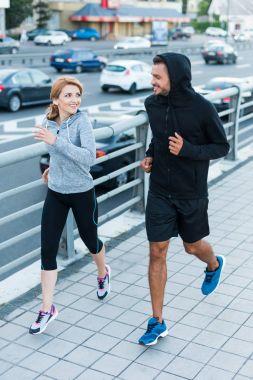 sportswoman and sportsman jogging in city