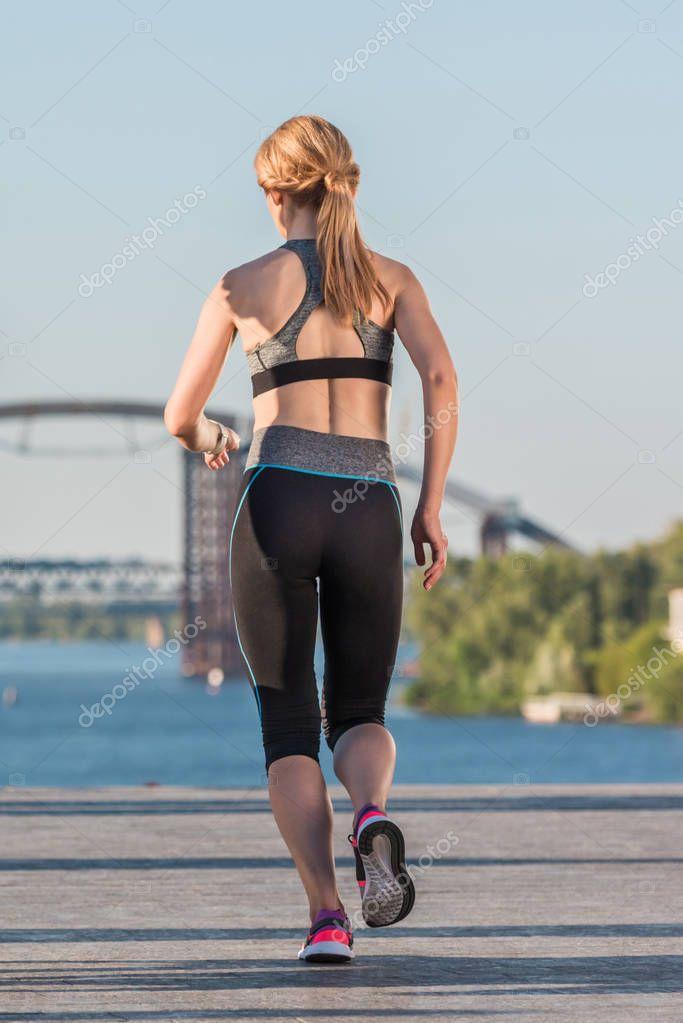 sportswoman running on quay