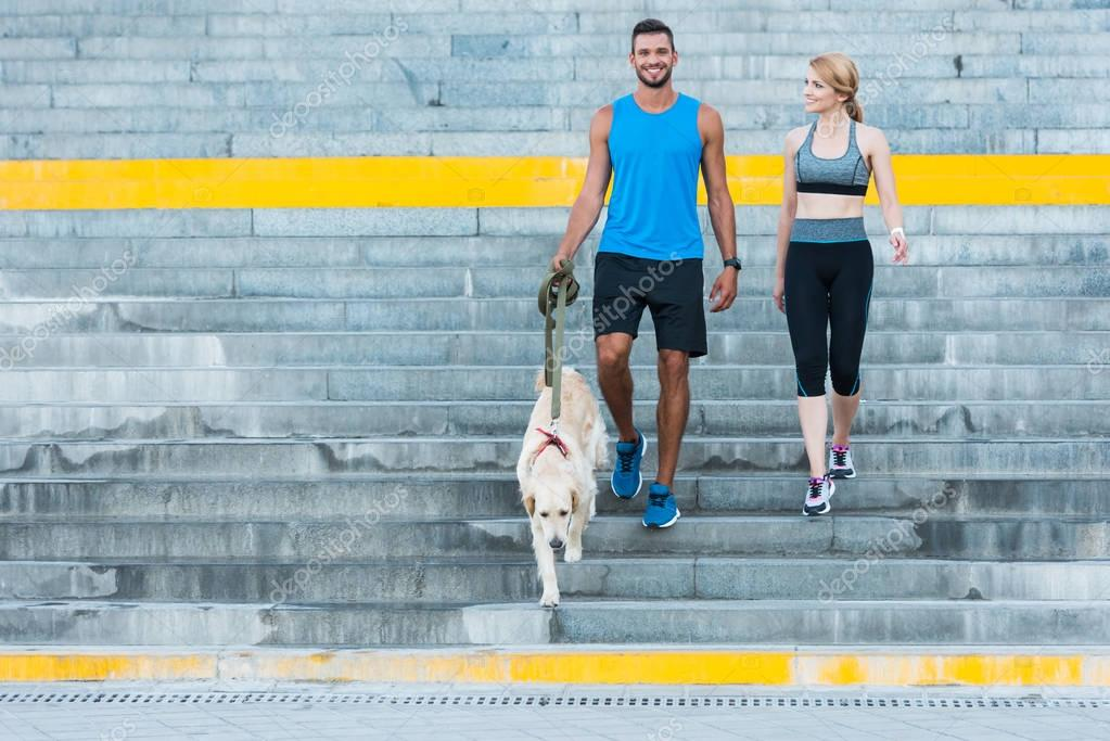 sports couple walking with dog