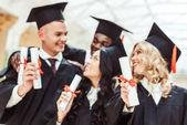 multiethnische Studenten mit Diplomen