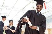 Fotografie dělené student ukazující diplom