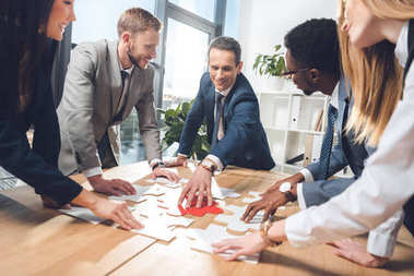 businesspeople assembling puzzle together
