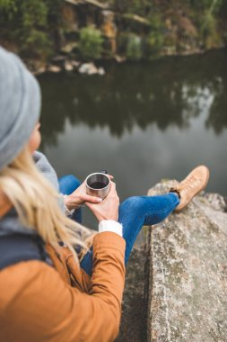woman with cup of tea sitting on rock