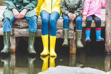 family sitting on wooden bridge
