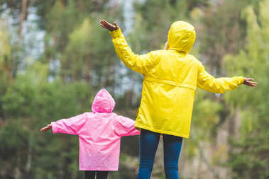 family in raincoats with outstretched arms