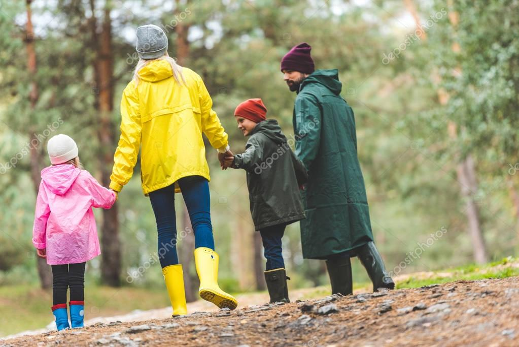 family in raincoats walking in forest