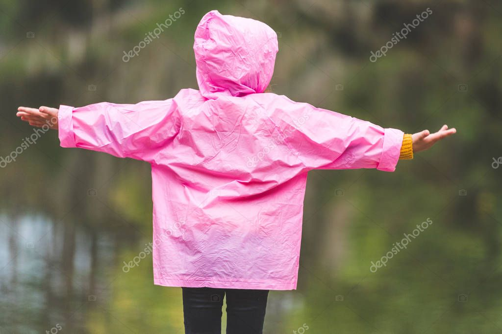 kid in raincoat with outstretched arms