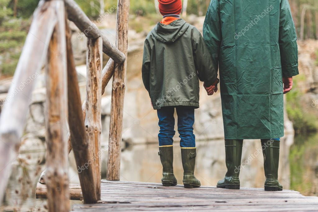father and son standing on bridge in forest