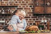 Großmutter und Enkelin umarmen sich in der Küche
