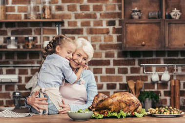 grandmother and granddaughter embracing on kitchen