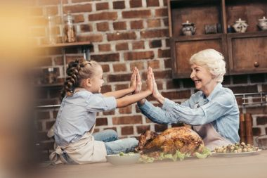 grandmother and granddaughter giving high five
