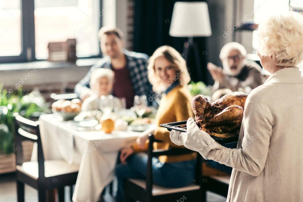 senior woman carrying thanksgiving turkey