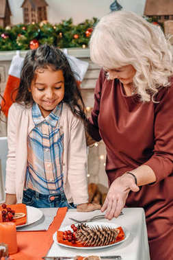grandmother decorating christmas table with granddaughter