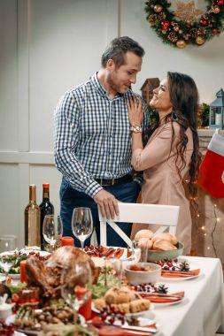 couple embracing next to christmas table