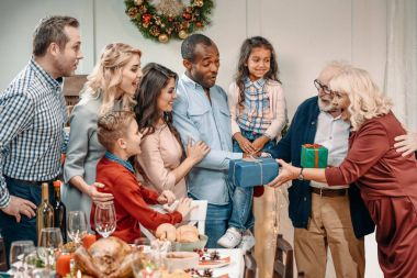 grandparents presenting gifts to family