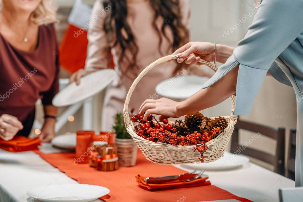 women decorating christmas table with berries