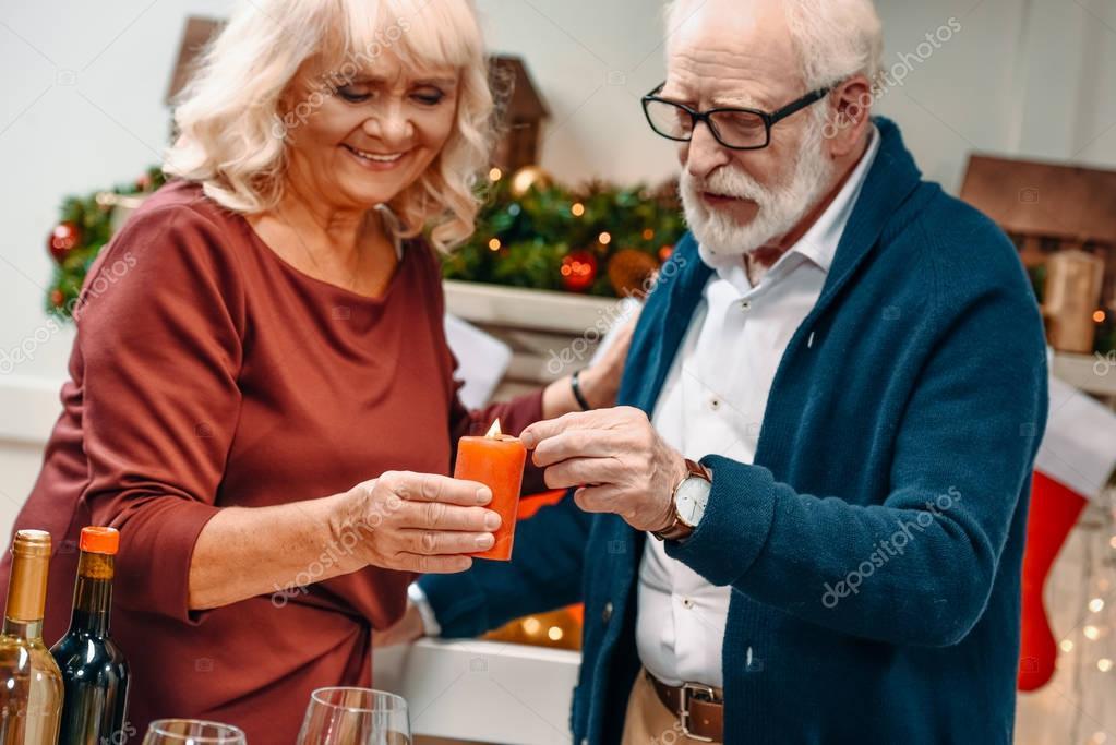 senior couple holding candle