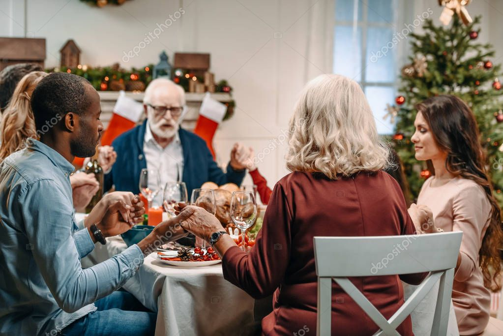 family praying before christmas dinner