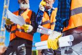Stavební dělníci drží stavební plány
