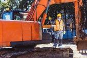 Stavební dělník pózuje s bagrem