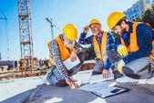 stavební dělníci s stavební plány