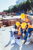 Stavební dělníci zkoumání stavební plány